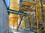 Radial movement conveyor for dual feeding from concrete plant